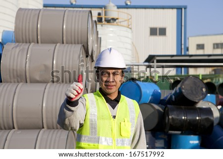 Worker giving a thumbs up approval success gesture on drum warehouse - stock photo