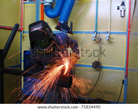 worker grinding pipe before weld - stock photo