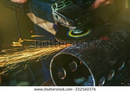 Worker grinding steel pipe in workshop, sparks flying around - stock photo