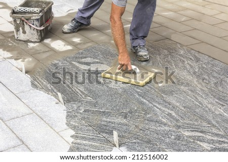 Worker grouting tiles with rubber trowel and gray cement mortar  - stock photo