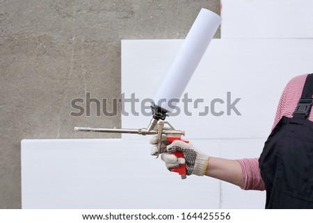 Worker hand holding polyurethane expanding foam glue gun applicator - stock photo