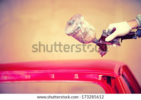 Worker hand painting a red hood of car in auto workshop - stock photo
