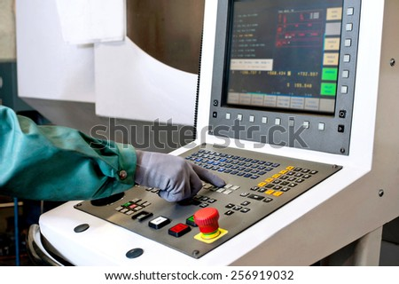 Worker hands on the control panel of a computer numerical control programmable machine. Milling and lathe industry. CNC technology. Metal engineering. - stock photo