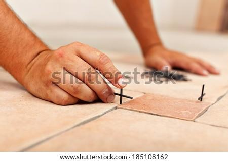 Worker hands placing spacers between ceramic floor tiles - close up - stock photo