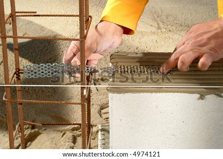 worker hands while aligning a metal plate over a concrete block