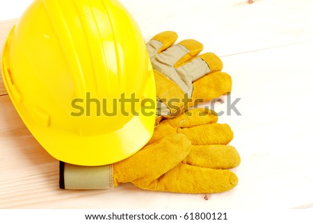 Worker hard hat and gloves over wood plank. - stock photo