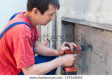 Worker have fixes the fastening in niche for radiators  - stock photo