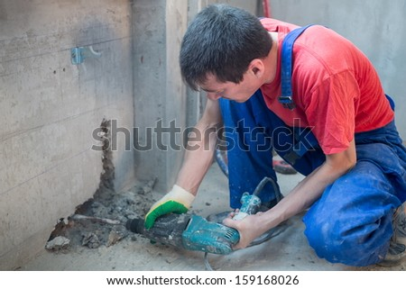 Worker have made a niche for radiators in apartment with a rough finish - stock photo