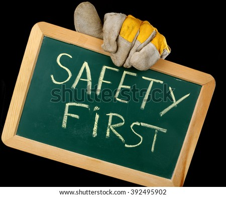 worker holding a board with the inscription SAFETY FIRST