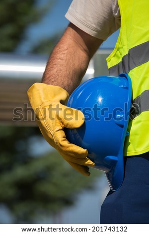 worker holding blue helmet - stock photo