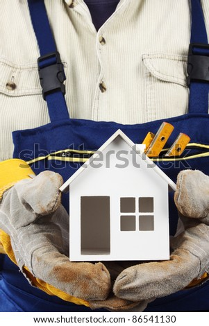 Worker holding house model in hand. Real property or insurance concept - stock photo