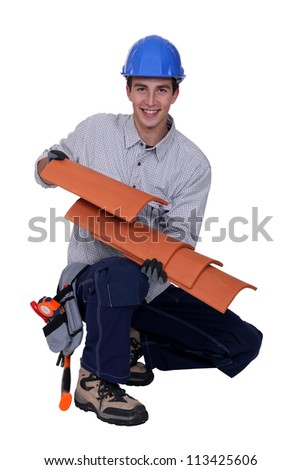 Worker holding roof shingles - stock photo