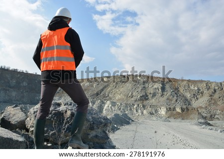 Worker in a helmet and quarry in background - stock photo