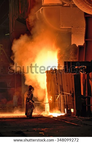 worker in a steel making factory taking sample from oven - stock photo