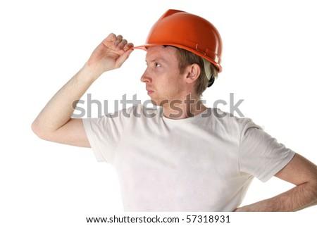 Worker in an orange helmet looks into the distance - stock photo
