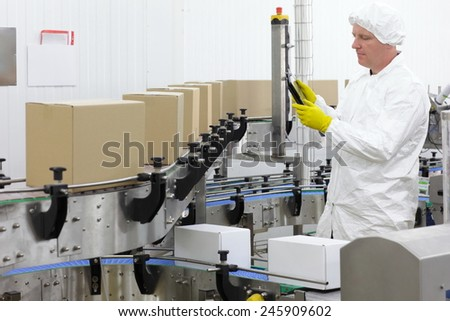 worker in apron, cap, gloves with tablet checking process at production line in factory. - stock photo