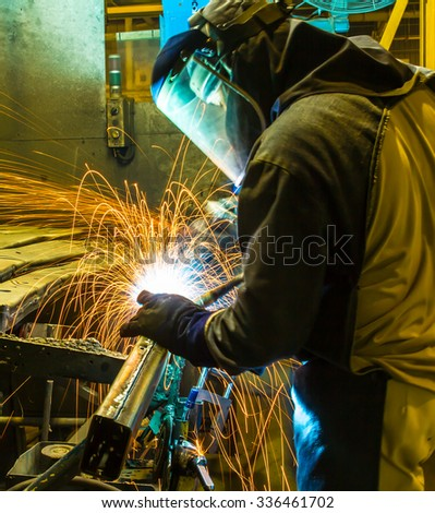 worker in automotive industry,welding working repair and grinding parts. - stock photo
