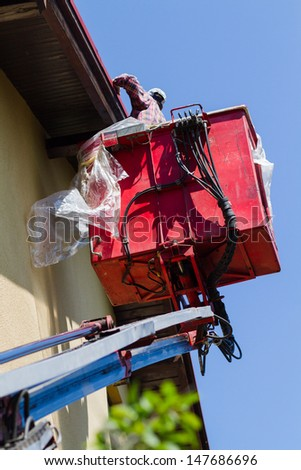 Worker in basket of the special car-lift - stock photo