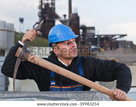 Worker in blue hard hat standing against industrial background