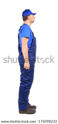 Worker in blue overalls. Side view. Isolated on a white background.