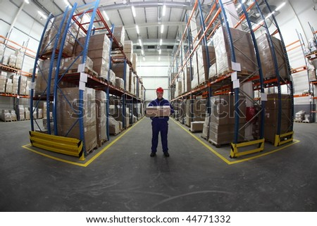 worker in blue uniform with box in the warehouse - stock photo
