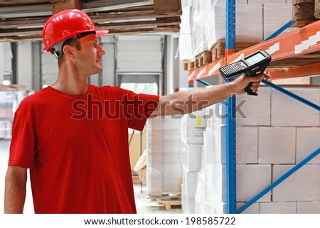 Worker in distribution warehouse with handheld barcode scanner - stock photo
