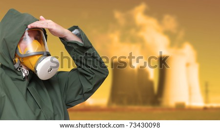 Worker in gas mask and chemical splash suit against a radioactive air pollution. Environmental hazard metaphor. - stock photo