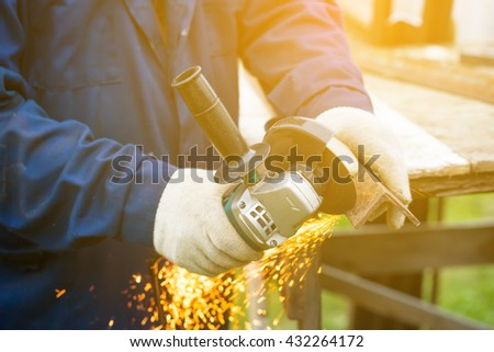Worker in gloves cutting a steel rail with angle grinder - stock photo