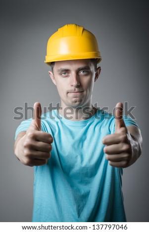worker in helmet thumbs up - stock photo