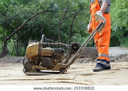 Worker in orange overalls with a plate compactor - stock photo