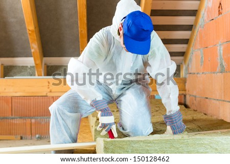 Worker in overall is cutting insulating material with gloves and knife  - stock photo