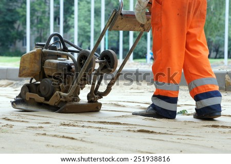Worker in overalls controls plate compactor - stock photo