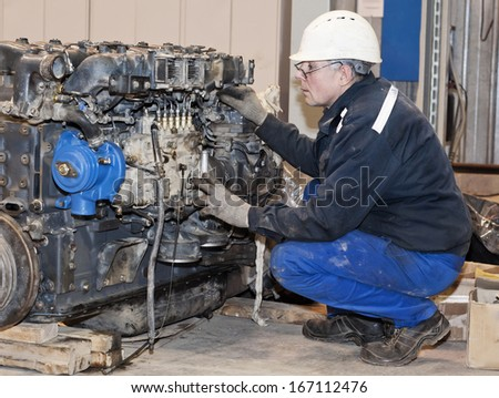 worker in protective clothes repairs an engine. - stock photo