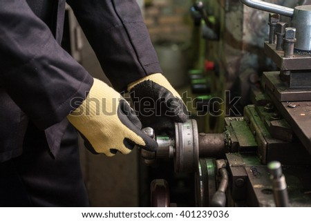 worker in protective gloves in factory using machine - stock photo