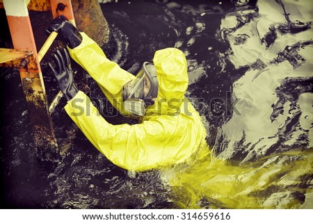 worker in protective suit in sea reaching ladder to save his life - stock photo