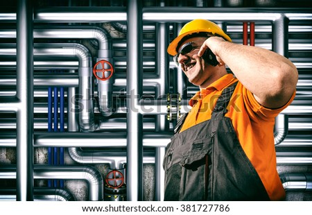 Worker in protective uniform and protective helmet in front of industrial pipes - toned image