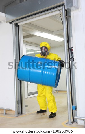 Worker in protective uniform,mask,gloves and boots lifting barrel of toxic substance - stock photo
