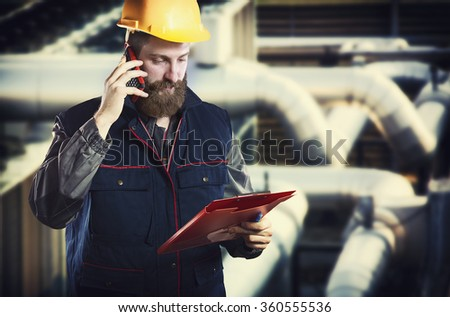 worker in protective uniform with smart phone and clipboard in front of industrial pipes - toned image, retro film filtered in instagram style - stock photo