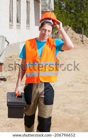 Worker in protective vest and hardhat at construction site - stock photo