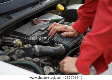 Worker in red overalls thinking over car engine - stock photo