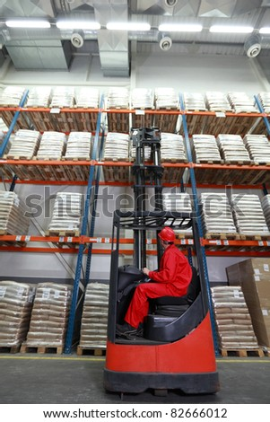 Worker in red uniform and safety helmet loading sacks with forklift loader in warehouse - stock photo