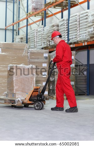 worker in red uniform at work  with hand powered pallet jack in warehouse - stock photo