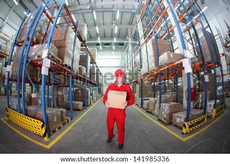 worker in red uniform with box in the warehouse in fish-eye lens - stock photo