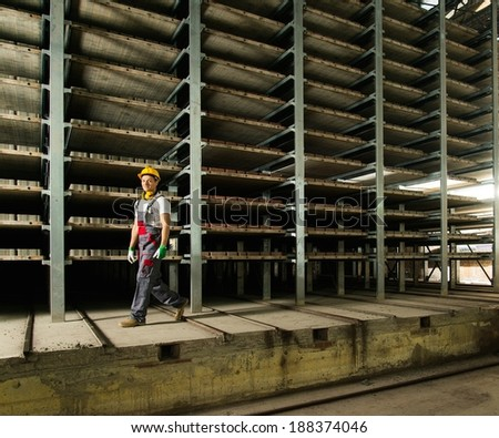 Worker in safety hat walking in a storage room on a factory - stock photo