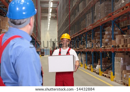 worker in uniform and hardhat carrying box, other looking at him. - stock photo