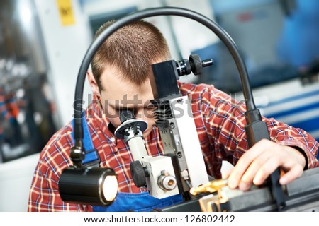 worker in uniform checking quality of countersink reamer sharpening using precise optical device - stock photo
