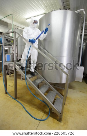 worker in white protective uniform,mask,gloves with high pressure washer on stairs at large industrial process tank preparing to cleaning - stock photo