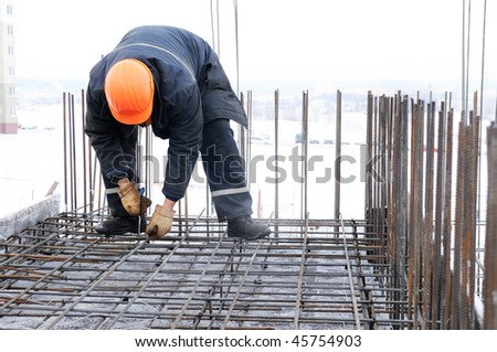 worker in workwear making reinforcement metal framework for concrete pouring - stock photo