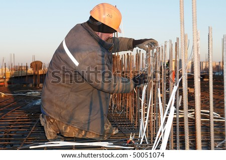 worker in workwear making reinforcement metal framework lattice for concrete pouring - stock photo