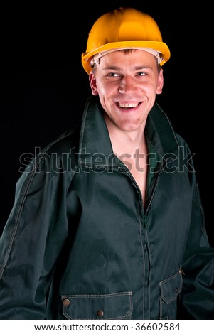Worker in yellow hard hat. Isolated on black. Studio shot. - stock photo